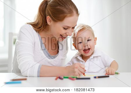 Mother with the baby son with colored pencils and laugh