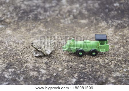 Green steel toy train route interrupted by a stone conceptual photo