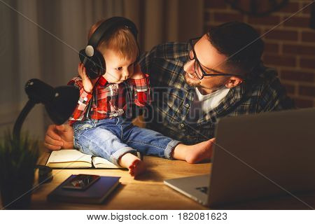 family father and son baby listening to music with headphones in the dark night