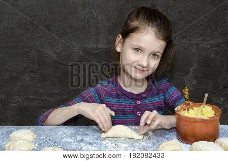 Little girl sculpts potato pies. The gray background.