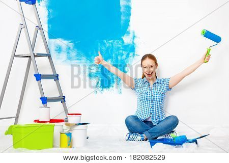 Repair in the apartment. Happy woman paints the wall with blue paint