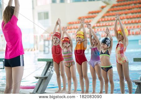 Instructor and group of children doing exercises near a swimming pool.