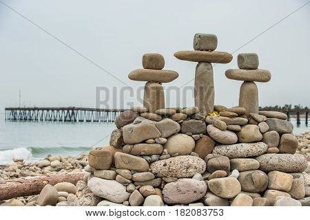 Stone crosses made of balanced rock on Ventura beach with pier in background.