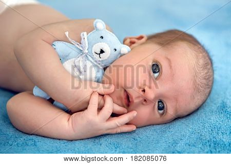 newborn lies with the blue soft toy bear on the bed on her back