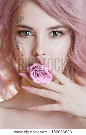 Colored hair.Beauty women portrait of young curly woman with pink pastel colored hairs, manicure and perfect art make-up with glitter. Rose in her mouth. Studio