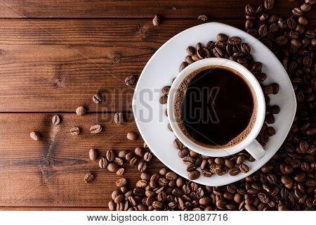 Coffee cup with saucer and beans on wooden table. Top view.