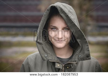 Beautiful pretty lovely girl in the hoodie smiles at the street in cloudy weather in russia