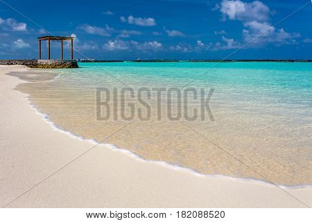 Closeup of water at Maldives with a gazebo in the background