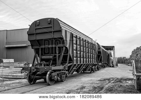 Maritime transportation industry. Railway freight wagons in the port warehouse area waiting for unloading the goods.