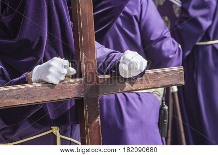 Penitent dressed in purple tunic of velvet resting on wooden cross during atonement station on Holy Week Andalusia Spain