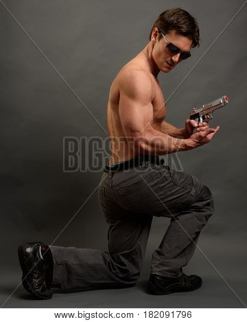 The handsome military man is crouched down with a pistol.