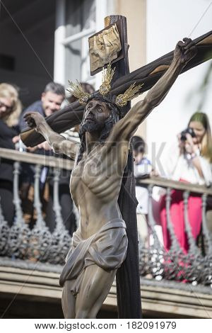 Linares, SPAIN - April, 14: Figure of Jesus on the cross carved in wood by the sculptor Gabino Amaya Guerrero, Holy Christ of the expiry,processions through the streets, the people overlooking the windows to see up close, Linares, Jaen province, Spain