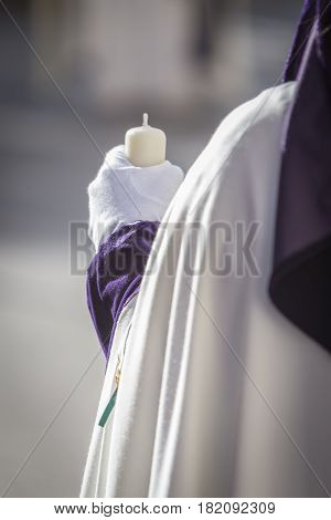 Detail penitent white holding a candle during Holy Week Spain