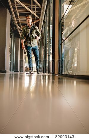 Full length shot of young man skateboarding in office. Casual businessman skating through office corridor.