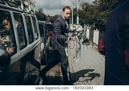 Stylish Groom Getting Out From Retro Car, Walking With Modern Bouquet To Bride In The Morning, Weddi