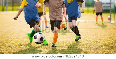 Kids Playing Soccer Game Tournament. Football Soccer Match for Children. Boys Running and Kicking Football. Youth Soccer Coach in the Background