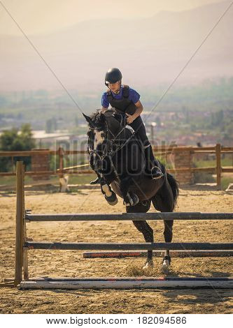 Equestrian sports Black horse approaching.The jump shooting from the front. Jockey riding a fast thoroughbred horse