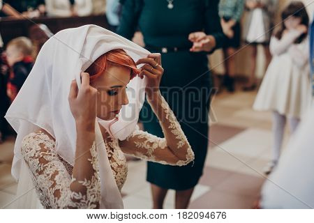 Stylish Bride Putting On White Scarf And Praying During Matrimony Wedding Ceremony In Church. Emotio