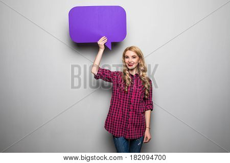 Cheerful Attractive Young Woman Standing And Holding Blank Speech Bubble Over Grey Background