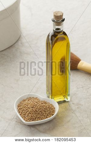 Glass bottle with mustard oil and a dish with seeds for skin care