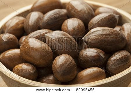 Wooden bowl with whole pecan nuts close up