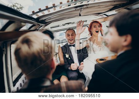 Stylish Happy Bride And Groom Having Fun And Dancing Inside Of Retro Car Smiling. Emotional Moment,