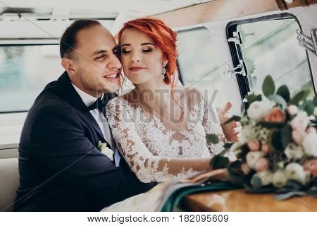 Stylish Happy Bride And Groom Embracing, Gently Hugging In Retro Car And Smiling. Emotional Moment,
