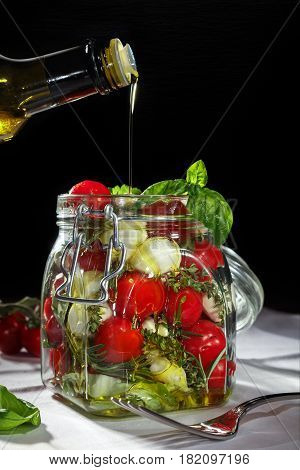 Oil pouring in a mason jar with fresh vegetables