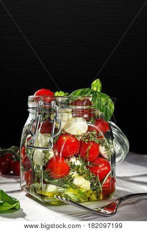 Mason jar with fresh mixed vegetables on dark background