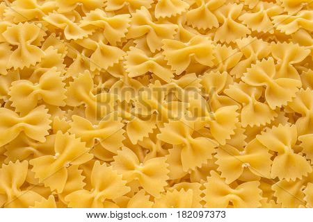 Food background made of raw Farfalle noodles from top view