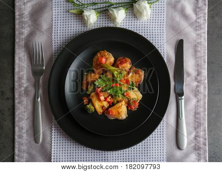 Plate of chicken stir fry with vegetables on table
