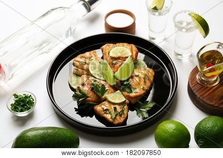 Plate of delicious tequila lime chicken with ingredients on white background