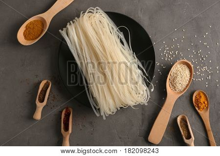 Plate with rice noodles and spices on gray background