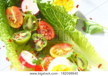 Overhead of lettuce leaves with cherry tomatoes baby kiwi fruits radishes and boiled eggs with red pepper flakes