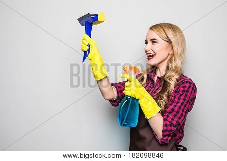 Portrait Of Attractive Young Woman Cleaning Windows Isolated On Grey