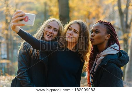 Three attractive happy woman making selfie in autumn park. Pretty girls with different colored skin. Female making funny faces