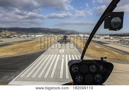 Burbank, California, USA - April 12, 2017:  Airport runway approach with afternoon clouds in Southern California.