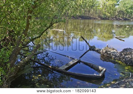 Immersed old damaged wooden boat in the river bed.