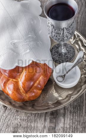 Wine, challah on a wooden surface for the Jewish Sabbath