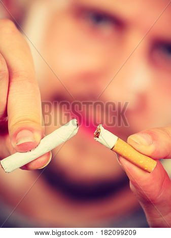 Young man breake down cigarette. Winning with addicted nicotine problems stop smoking. Quitting from addiction concept.