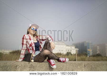 Beautiful young skater girl posing with a skateboard