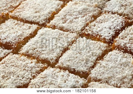 Fresh baked Moroccan yogurt cake cut into pieces decorated with white cocos full frame
