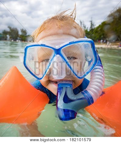 Boy with armbands, mask and snorkel plays in a sea