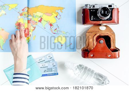tourist stuff with photo camera, hand and world map on white table background top view