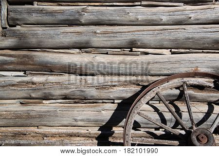 Hand cut logs barn wood from old cabin and wagon wheel background