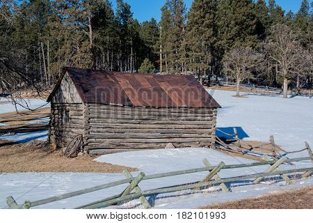 Historic log cabin with handhewn wooden logs and wagon wheel in winter