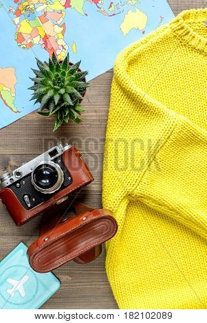 journey planning with tourist outfit and camera, map, clothes on wooden table background top view