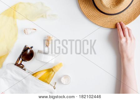 cream and lotion cosmetic for sun protection with hat in a sunbath concept on white background top view