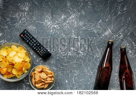 TV remote control, snacks, beer on dark desk background top view space for text