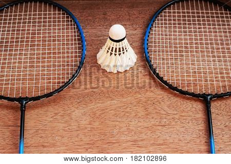 Badminton rackets and badminton balls are placed on a brown background